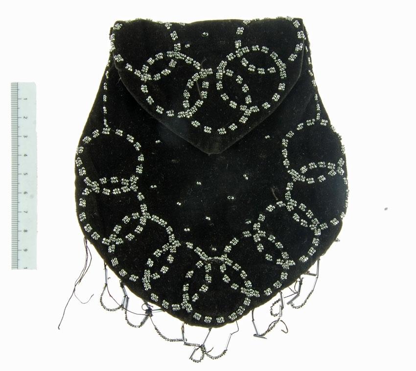 Anmärkningar: Irsta sn Geddeholm  Väska, 1 st, av svart bomullssammet fodrad med svart bomullstyg. Hjärtformad med litet lock att fälla ner, som stängs med en hake och hyska. På baksidan spår av att väskan varit fäst vid exempelvis ett smalt skärp. Framsidan dekorerad med cirklar av strasspärlor, nertill hängande öglor av upptädda strasspärlor. Innehöll en liten virkad svart pung inv.nr 29417.