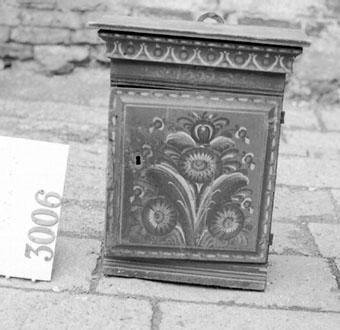 """Anmärkningar: Väggskåp av trä. Har rektangulär form med krön uppbyggt av urkälad list. Dörren är slät med utskuren kant och fästad på två gångjärn av järn. Dörren är försedd med lås av järn och har nyckelhålsbeslag av bly. Dörren lagad vid låset. Skåpet är inrett med ett hyllplan och har ett klackjärn för upphängning. Skåpet målad i rödbrun i """" kammad """" färg. På dörren är målad en kurbits i gröna nyanser, vitt och svart. På krönet dekor i vitt och grönt samt årtalet 1833.  I Liggaren står: """" Vid Kjellbergs besök. """"."""