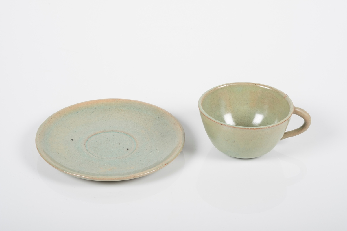 Kopp med skål i keramikk med grønn lasur. Buet hank på koppen. Koppen og skålen har spor etter tre knotter på bunnen, usikker funksjon. Bunnen på skålen har matt overflate.
