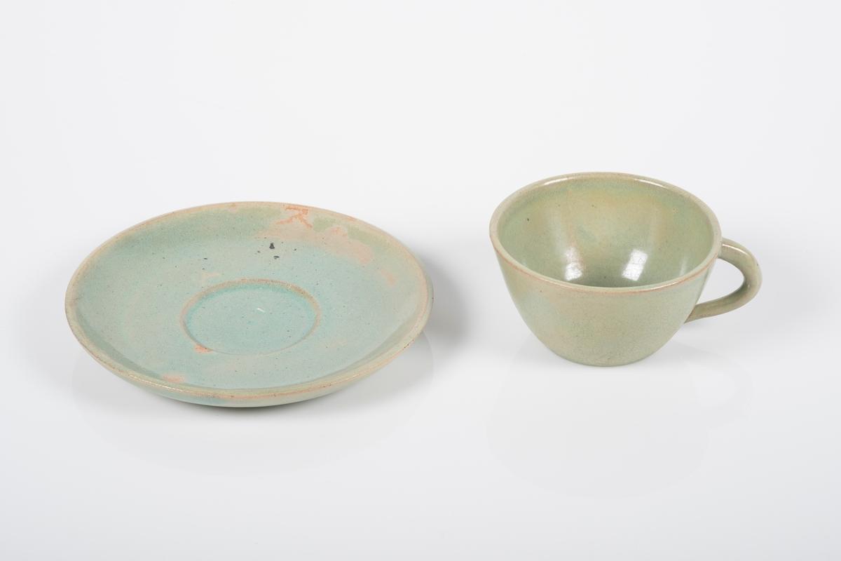 Kopp med skål i keramikk med grønn lasur. Buet hank på koppen. Koppen og skålen har spor etter tre knotter på bunnen, usikker funksjon. Bunnen på koppen og skålen har matt overflate.
