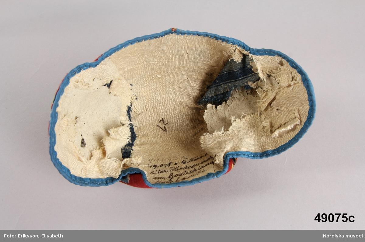 3 bindmössor av rödbottnad kattun. a. från Österfärnebo el. Hedesunda sn längd 37 cm från öra till öra b. från Österfärnebo eller Hedesunda sn. Längd från öra till öra: 37 cm. c.  a. av rödbottnad kattun dvs tryckt bomullstyg med blommönster i gult, blått , grönt och svart  kantad med ljusrosa sidenband, fodrad med blårutig linnelärft, dragband i nacken av linnesnodd.  b.samma tyg som a.fodrad med oblekt linnelärft, rest av tvinnad linnesnodd i nacken. c.  Berit Eldvik mars 2005