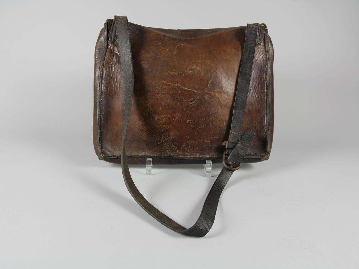 Postväska, rektangulär, av brunt skinn med reglerbar bärrem. Smal klaff/fällock som låses med fyra metallöglor och lång rund metallten.