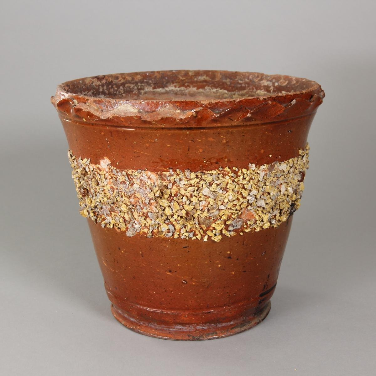 Blomkruka av brunglaserat lergods. Profilerad kant vid mynningen. Bård av brun och vit krukskärv.