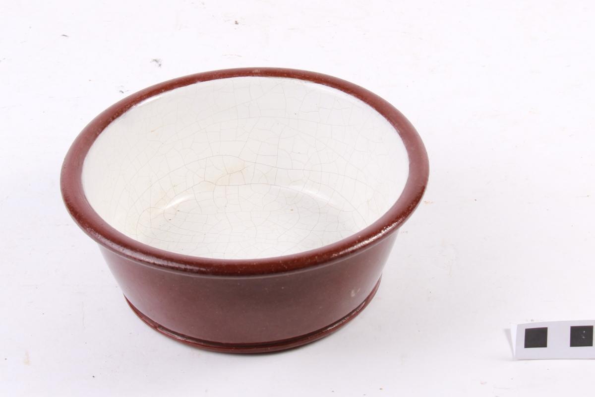 Brun glasur utanpå og kvit innvendig. Den kvite glasuren er krakkelert.