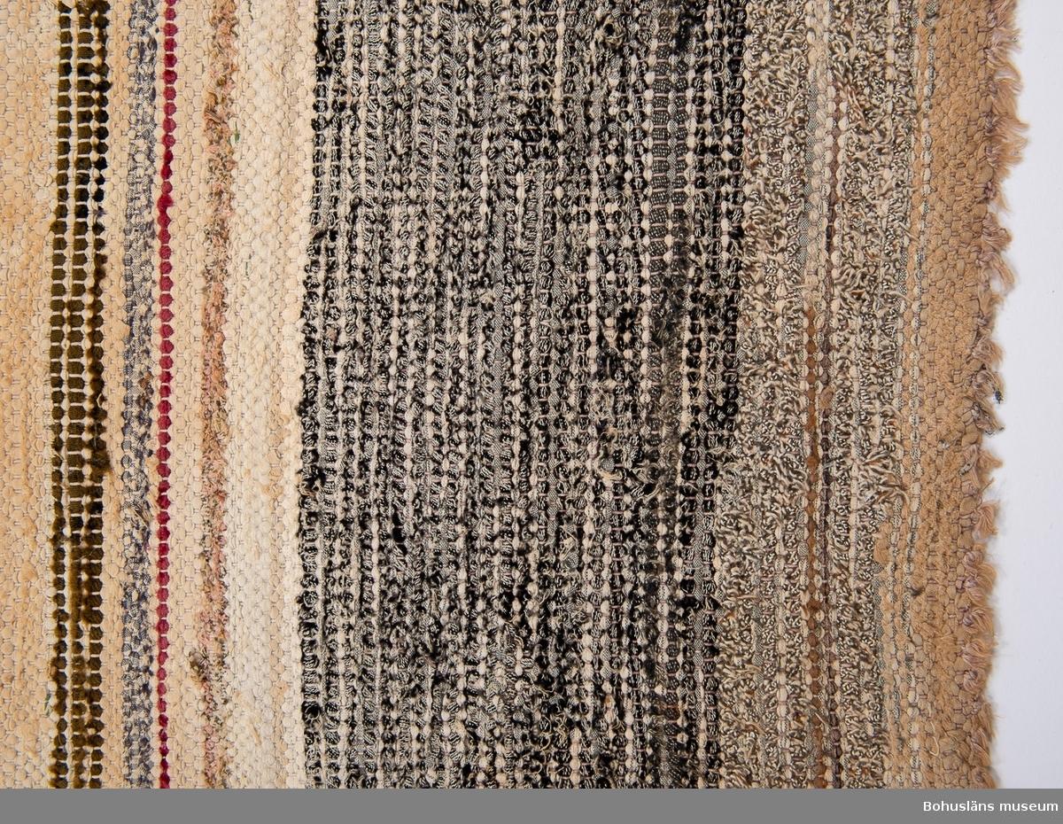 Inslag i mörka och ljusa färger. Inga direkta avgränsade partier.  Blekta och urtvättade färger. UM021228:001 - UM021228:003 har liknande mönster.