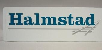 """Rektangulär plastskylt med blågrön text på vit botten: """"Halmstad"""". Grått streck under texten, som avslutas med ett järnvägsspår på höger sida om texten. Järnvägsspåret är bolaget Sydvästens logotyp.  Historik: Företaget fanns mellan 2000-01-01 till 2000-05-31 då det gick i konkurs."""