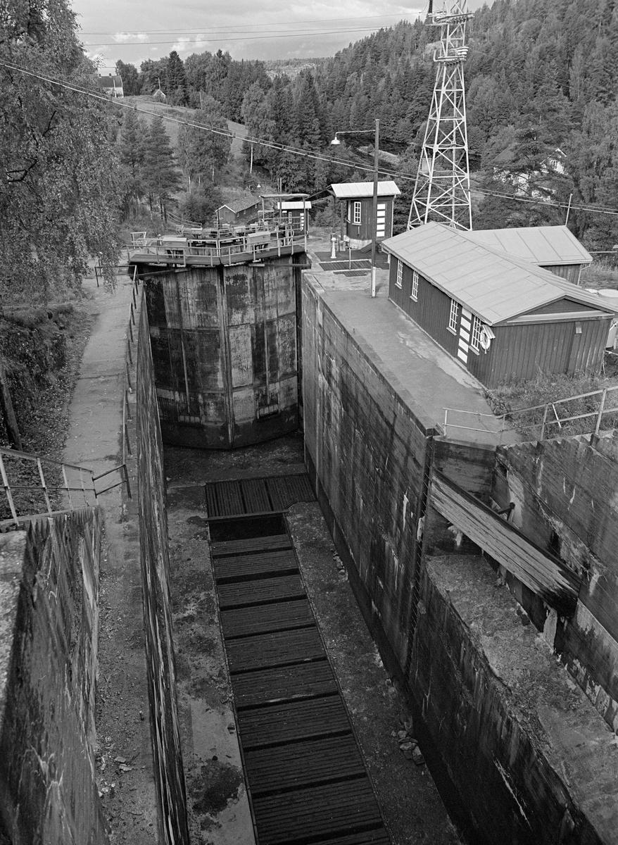 Tørt slusekammer ved Brekke sluser i Stenselva i Haldenvassdraget høsten 1982.  Fotografiet er tatt fra plattformen ved ovenforliggende slusekammer, i et slags fugleperspektiv.  Dermed ser vi godt ned i slusekammeret, som hadde glatte, betongstøpte sidevegger og en kanal i golvet med overliggende spalterister.  Når slusekammeret skulle fylles med vann fra ovenforliggende kammer, ble det ført via omløpsrør som gikk forbi sluseporten og inn gjennom denne kanalen.  Løsningen med omløpsrøret, kanalen og ristene skulle gi ei oppfylling av slusekammeret uten nevneverdig bølgedannelse, noe som kunne være et problem når tappinga skjedde via luker i sluseportene.  Også stålportene i Brekke-slusene hadde slike luker, men de ble bare brukt til finjustering av vannstanden.  Bygningen på plattformen til høyre for slusekammeret er Haldenvassdragets kanalselskaps verkstedbygning.  Brekke sluser har en løftehøyde på hele 27 meter fordelt på fire slusekammere, alle med porter av stål.  Dette er det tredje sluseanlegget som ble bygd ved Brekke.  Det første, som den kjente vassdragstekniske pioneren Engebret Soot (1786-1859) hadde idéen til, ble bygd i slutten av 1850-åra av stedlig stein med rosentorv som tettingsmateriale i murverket.  Dette sluseanlegget ble ødelagt under flom alt i 1861.  I perioden 1873-1877 bygde det statlige Kanalvesenet et nytt sluseanlegg ved Brekke, også dette med fire slusekamre, men åpenbart mer solid enn det første.  Fredrikshald (Halden) kommune sikret seg fallrettigheter ved Brekke alt i 1904.  Det varte imidlertid helt til 1918 før kraftutbyggingsprosjektet her ble påbegynt.  I åra som fulgte ble det bygd en massiv betongdam ved Brekkefossen som var 110 meter lang, og som på grunn av vanskelige grunnforhold måtte få en høyde på opptil 38 meter.  Kraftverksdammen hevet med andre ord vannspeilet i den ovenforliggende delen av Stenselva kraftig, slik at det ble nødvendig å bygge et helt nytt sluseanlegg.  Dette ble altså utført i armert betong, med stålpo