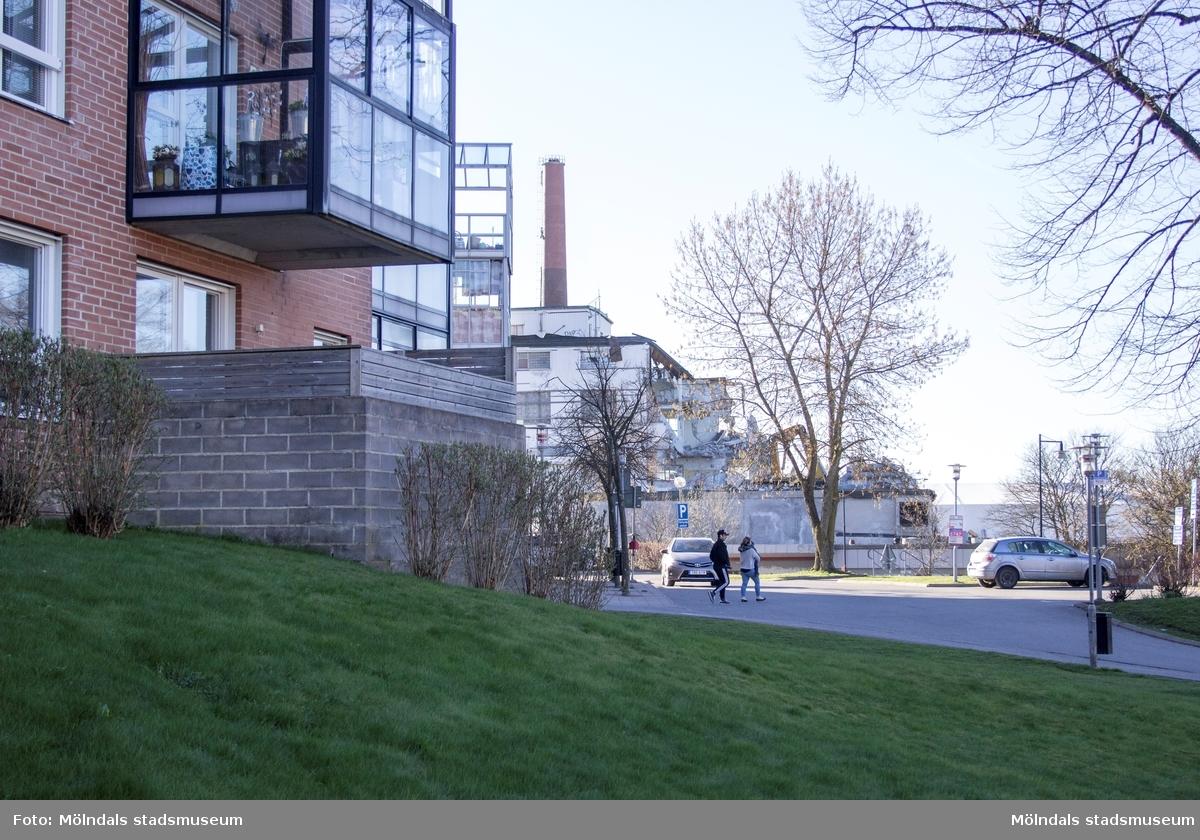 Byggnadsdokumentation av Papyrusskorstenens rivning 2015-05-08. Byggnad 6 (kartongfabriken) ligger strax framför. Relaterade motiv: 2018_0110 - 0116. Till vänster ses flerbostadsområdet Silverskatten på Störtfjällsgatan.