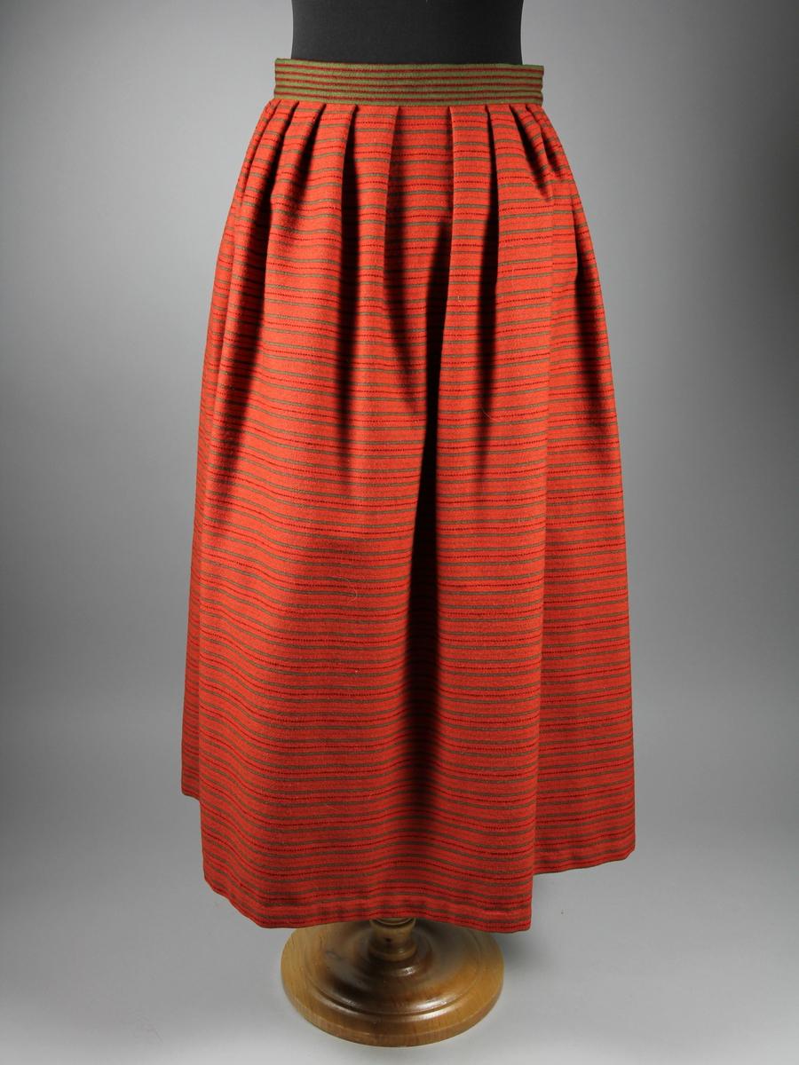 Underkjol till Häverödräckten. Tvärrandig halvyllekjol av ett stycke. Röd botten med smala ränder i grönt och svart. Kjolens breda linning är sydd av ett annat randigt halvylletyg med röda och svarta ränder på grön botten. Liningen stängs med ett handvävt band av grövre ullgran. Mot linningen är kjolen lagd i breda veck. Kjolens sprund är förstärkt med langettstygn i botten. Kjolen är handsydd.