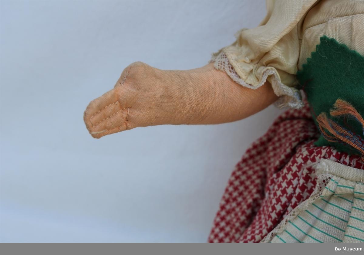 Dokke med celluloidhovud, tøykropp og garn til hår samla i to fletter. Dokka har på seg strømper, sko, mamelukker med sløyfer og blonder, trøye med puffermer og to knappar, korsett med snøring framme, rutete skjørt med underskjørt og stripete forklede med blonder og påsydd band med prikkar. Forkledet er laust i eine sida. Den har øredobbar og blomemønstra skaut på hovudet. Ansiktet er måla på. Dokka lagar skrikelyd når ein slår på brystet. Hendane er ein klump med sømmer som definerer fingre.