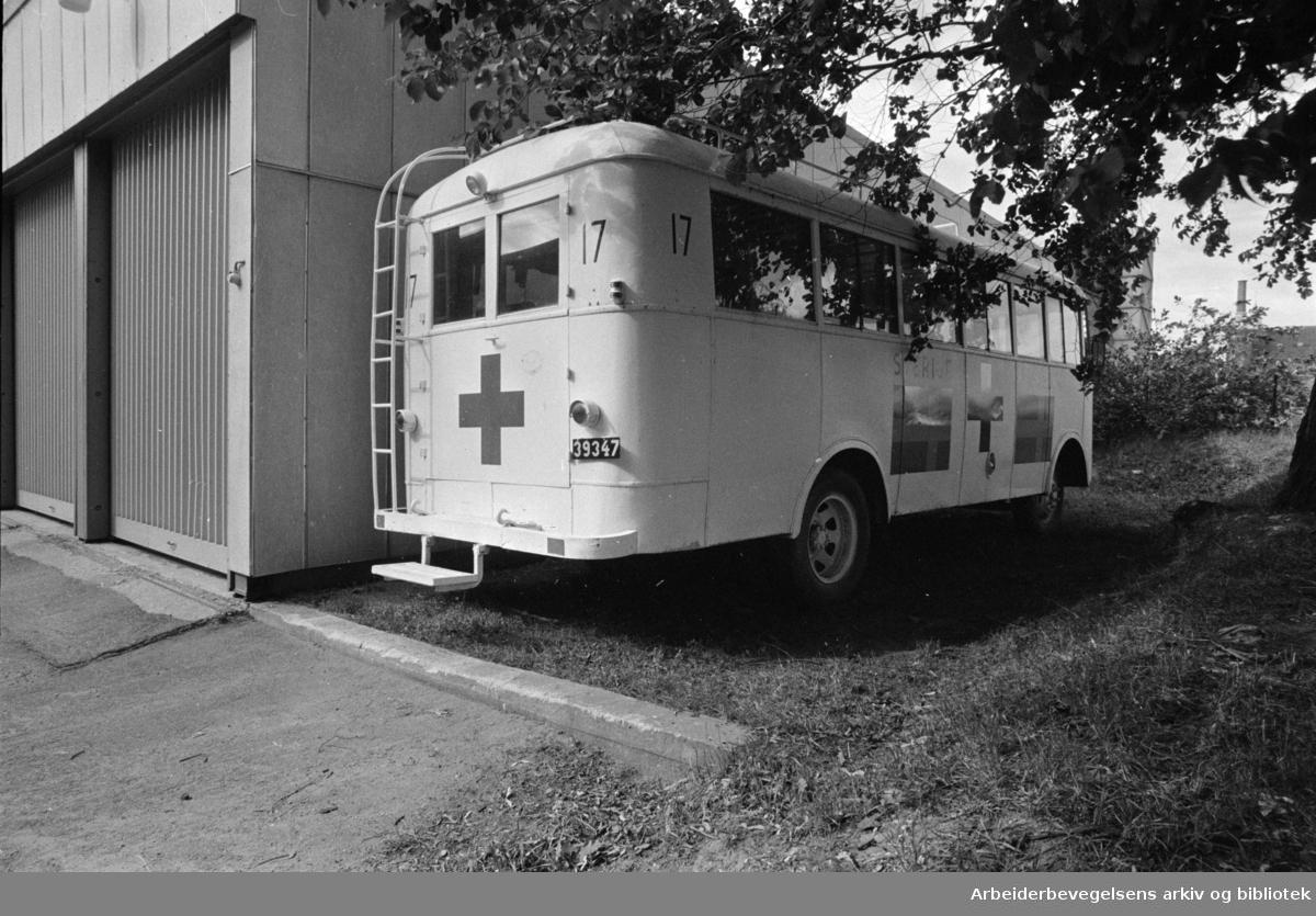 """Oslo: Akershus Festning. """"Den hvite bussen"""" står godt bortgjemt på Akershus. Skal inn på Hærmuseet (Forsvarsmuseet) til høsten. De hvite bussene, Røde Kors.Juli 1970"""