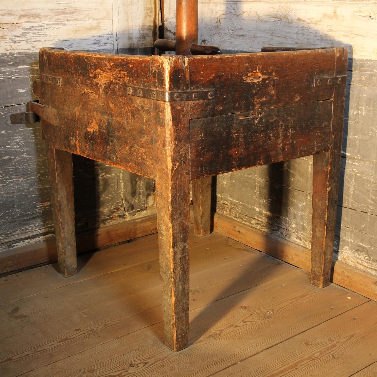 Kvadratisk ställning av trä med fyra ben. I hörnen vinkelbeslag av järn. Rester av brun färg. I ställningens botten runt hål med två korsade järnband för försänkning av gryta (SKANM.0105226A). Ställningen fäst i väggen.