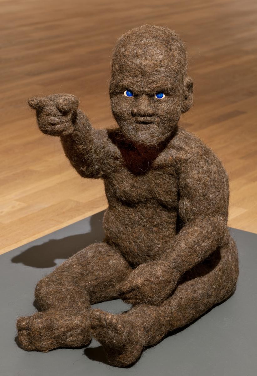 """Skulptur med stomme av frigolit och ytan av filtad ull. Detaljer av målad cernitlera (ögon och kön). Figuren är en sittande """"mänsklig"""" gestalt av """"en annan art""""."""