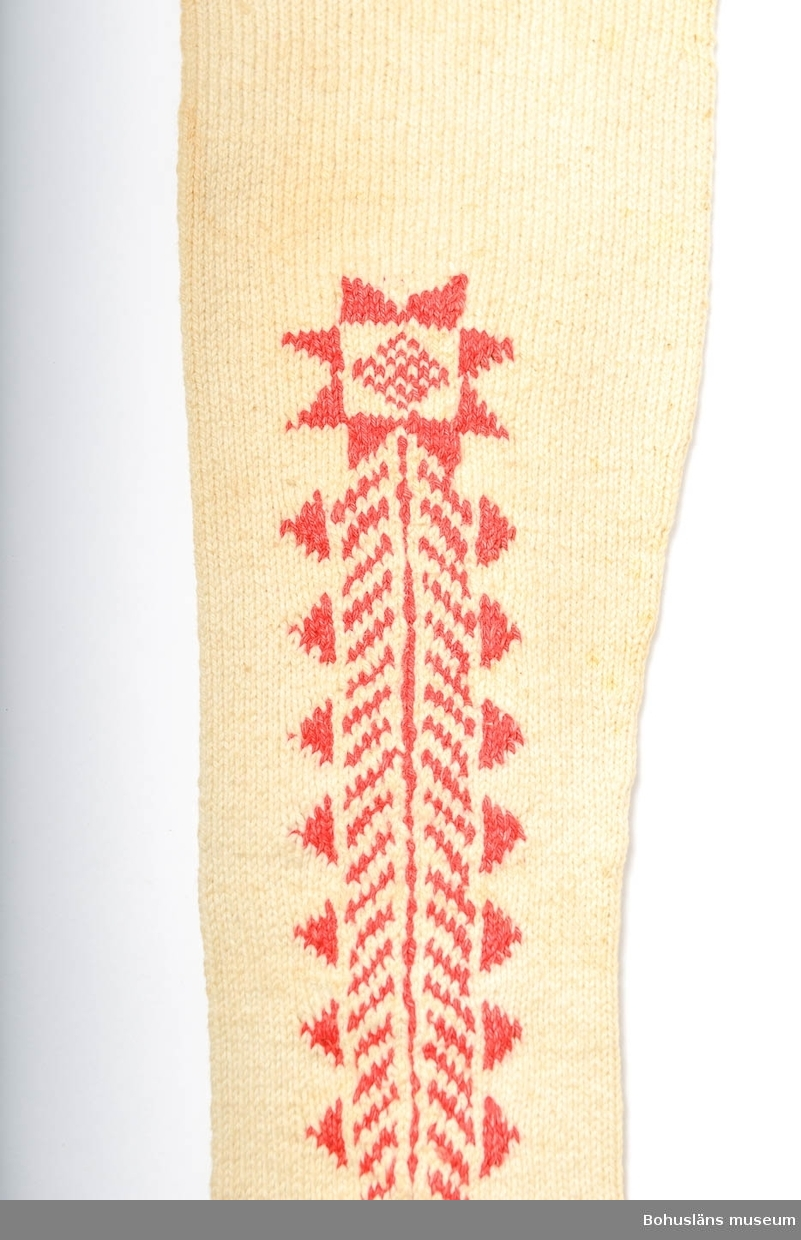 """Handstickade strumpor av bomullsgarn. Vita med instickat geometriskt mönster i rött längs fötterna och upp på skaften, på båda sidor. Slätstickade med en kant mönstrad av aviga och räta maskor i diagona ler överst. Märkta UM 4:C:I och II. Enligt Knut Adrian Anderssons katalog I:5:4, D 2 A:1 i museets arkiv, är strumporna """"stickade ur minnet av en gammal kvinna på Inland i början av 1900 talet"""". I samma katalog står även att de vita strumporna skänkta 1910 av Bertha Kleberg är stickade av """"gummor på Inland"""". Svagt brungula fläckar på många ställen (rost?). Gulnade. Strumporna diskuteras och är avbildade i Centergran (2010) s. 27-28.  Litteratur om Bertha Kleberg och om revitalisering av bygdedräkter: Arill, David, Bertha Kleberg och Bohusdräkten ur Bohusländska folkminnen Studier och uppteckningar red Arill, David, Uddevalla 1922. Centergran, Ulla, Folkdräktsrörelsen i Bohuslän och Göteborg, C-uppsats i etnologi, Göteborg 1973, Bygdedräkter bruk och brukare, Göteborg 1996.  Centergran, Ulla. Bohusdräkter. Tolkningar under ett sekel. Bohusläns museum och Bohusläns hembygdsförbund, nr. 71. Bohusläns museums förlag. Andra upplagan 2010.  Wistrand P G, Bohusländska folkdräkter ur Fataburen häfte 1 1908. Omkatalogiserat 1997-03-20 VBT  Enligt uppgifter på diarienummer 184/69 KVINNLIGA DRÄKTPLAGG FRÅN BOHUSLÄN TILL UDDEVALLA MUSEUM: Strumporna 4a, 4b, 4c är stickade av gummor på """"Inland"""" i början av 1900-talet. ...  Ur handskrivna katalogen 1957-1958: Strumpor 3 par. a) Ett par a) 1-2 L. c:a 62 cm;röda, ylle, stickade m. resår i skaftets översta del; malhål.  b) ett par b:1-2; L. c:a 67 cm, ylle, vita m. instickade röda kilar; malhål.  c) Ett par c: 1-2; L. c:a 55; vita, bomull, m. instickade  röda kilar, några rostfläckar.   Lappkatalog: 78"""