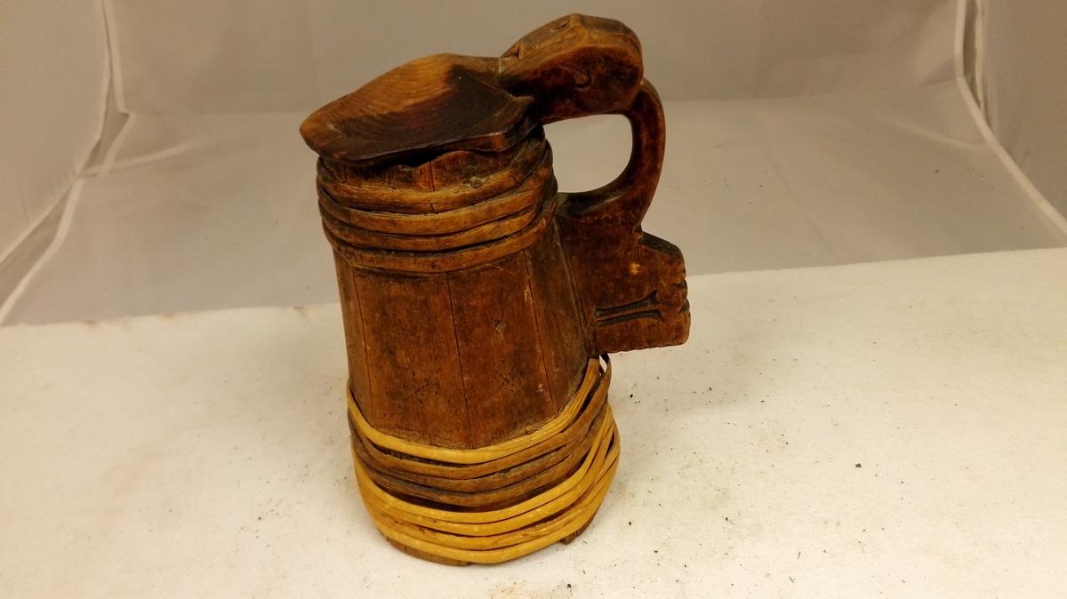 Form: Åttekanta. 1 lagget ölkande.  Ölkande lagget ottekantet av 8 furustaver 19,5 cm höie. Smalere överst end nederst.  Har laag, der er fæstet med trætapp til den profilerte hank, der er laget av en stav, den 9de. Överst og nederst 4 træband. Under bunden indskaaret bumærket (?) (sjå original).  Gave fra Jens Hansen Nornes, Norum.