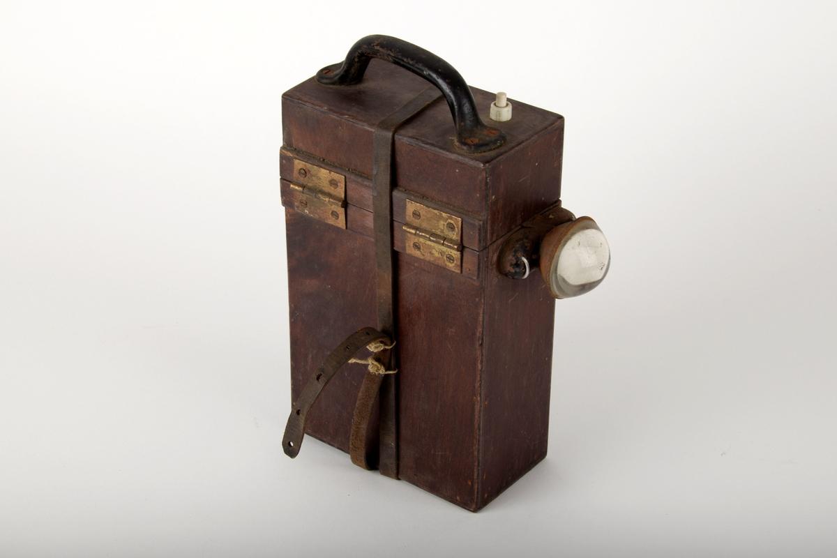 Lommelykt med trekasse. Lyktehodet er festet til fremsiden av kassen. Bærehåndtak og av/på knapp på toppen av kassen. Kassen kan åpnes ved å vippe av det hengslede lokket på toppen. Det går en lærstropp med spenne rundt kassen, slik at lokket holdes fast.  I kassen er to store batterier, som blir holdt fast av avispapir som er stukket ned mellom batteriene.