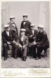 Ateljéporträtt - Sex män iklädda kostym och studentmössa, fy