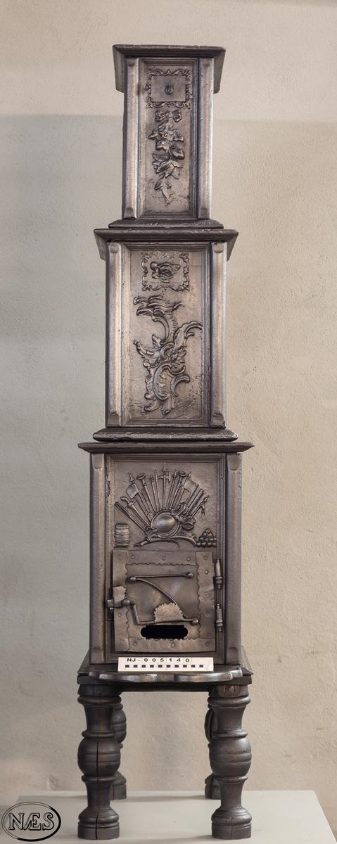 Ovn i 3 etasjer med hovedmotivet, Venus krever våpen til Æneas, på begge langsider 1. etasje.  Øverst på kortsidene 1. etasje krigerske emblemer. 2. og 3. etasje rokokko-ornamentik med uregelmessig åpning. Kortsidene med blad og blomster i sløyfe.