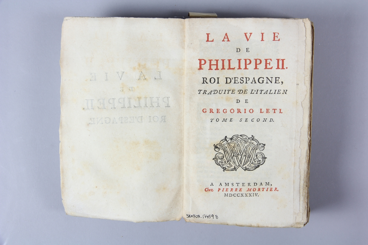"""Bok, häftad, """"La vie de Philippe II, roi d'Espagne"""", del 2, tryckt 1734 i Amsterdam. Pärm av marmorerat papper, oskuret snitt. Blekt rygg med etikett med titel och samlingsnummer."""
