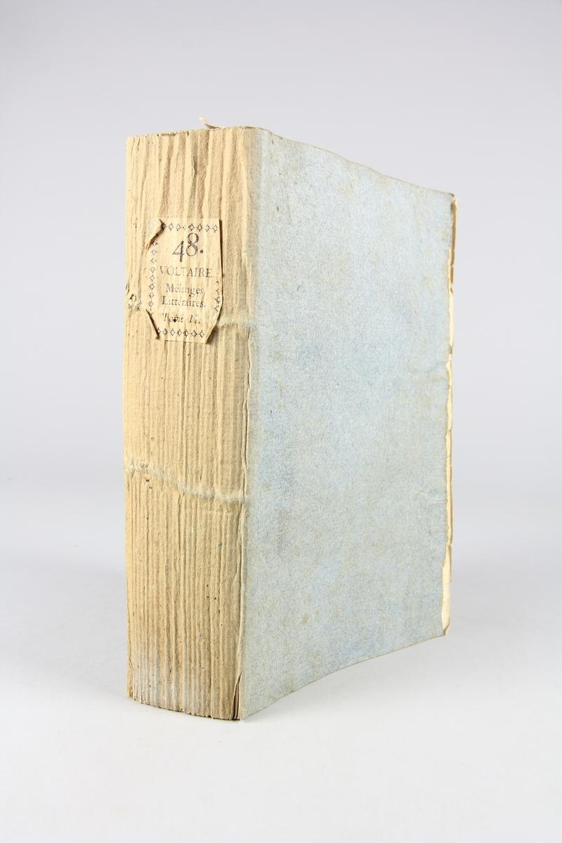 """Bok, pappband,""""Oeuvres complètes de Voltaire."""" del 48, tryckt 1785. Pärm av gråblått papper, skurna snitt. På ryggen pappersetikett med tryckt text med volymens namn och nummer. Ryggen blekt."""