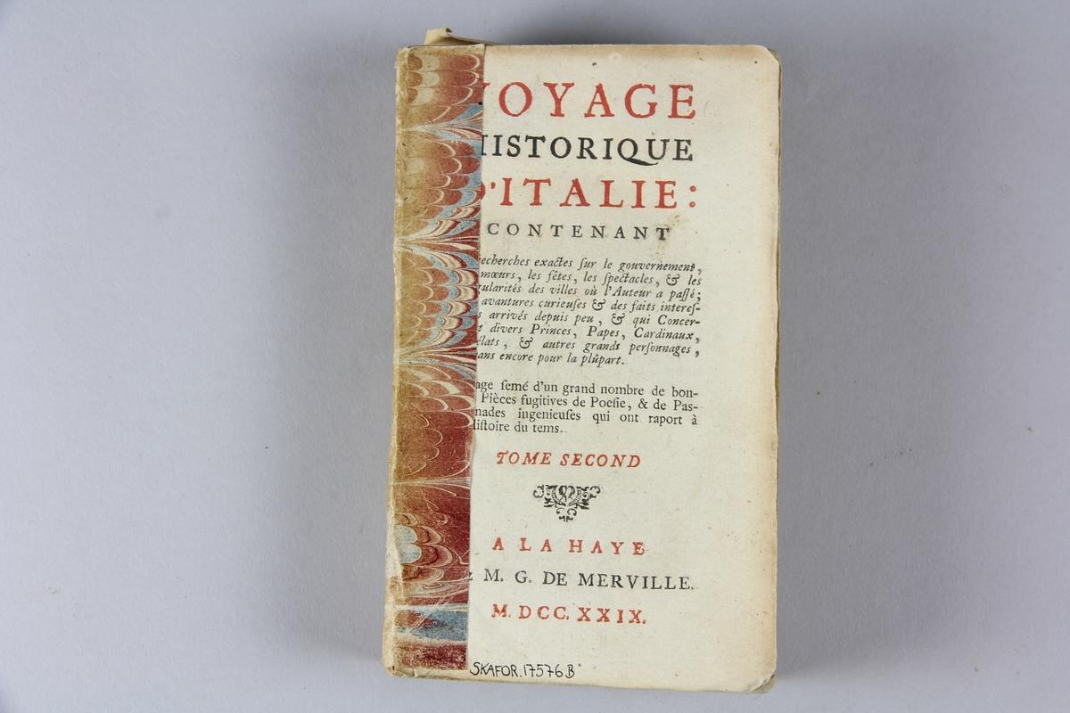 """Bok, häftad, """"Voyage historique d´Italie"""", del 2, tryckt 1729 i Haag. Pärmen av marmorerat papper, skadad, skuret snitt. På ryggen etikett med samlingsnummer."""