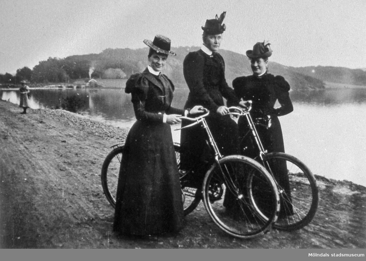 En cykeltur omkring år 1900. Tre damer fotograferade tillsammans med två cyklar på Strandpromenaden vid Stensjön i Mölndal. Till vänster ses Kerstin Svanfeldt (gift Stenström). Reprofotografi. ÖM 4:9.