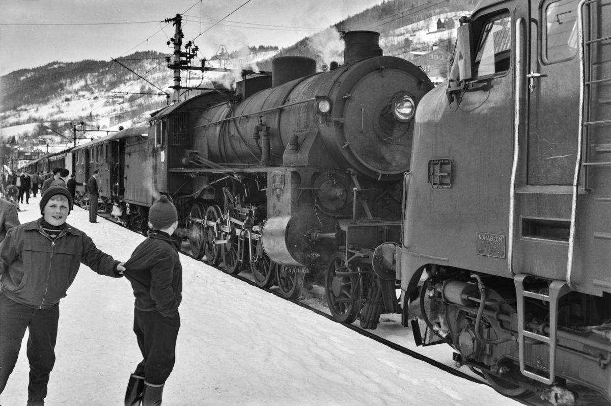 Dagtoget fra Bergen til Oslo Ø, hurtigtog 602, på Voss stasjon. Toget trekkes av damplokomotiv type 31b nr. 402 (forspann) og diesellokomotiv type Di 3 nr. 620 (ekstra forspann).