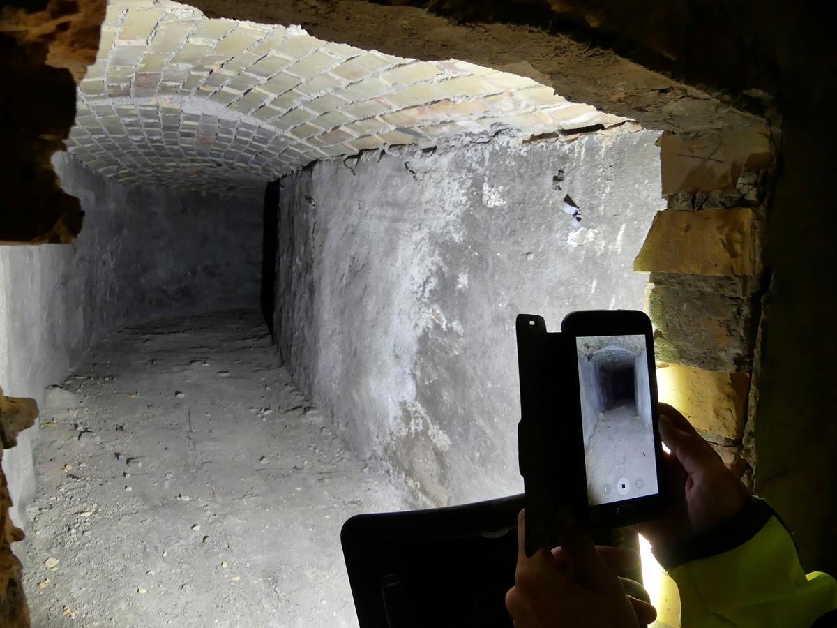 Arkeologisk schaktningsövervakning, tegelmurad gång under kyrkans kor, fotad murupptagning i nuvarande källare, Lena kyrka, Lena socken 2018