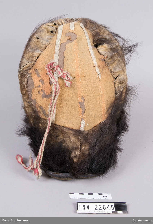 Grupp C I. Grenadjärmössa tillverkad av kartong med björnskinn spännt över på framsidan, medan baksidan är av rött ylle. Formen hålls uppe med hjälp av rottingpinnar. En filthatt med brätte är monterad innuti mössan. Runt mössans nederkant, ovanför brättet har det suttit en mässingskordong som nu är borta. På baksidan sitter en röd och vit banderoll som är trasig.