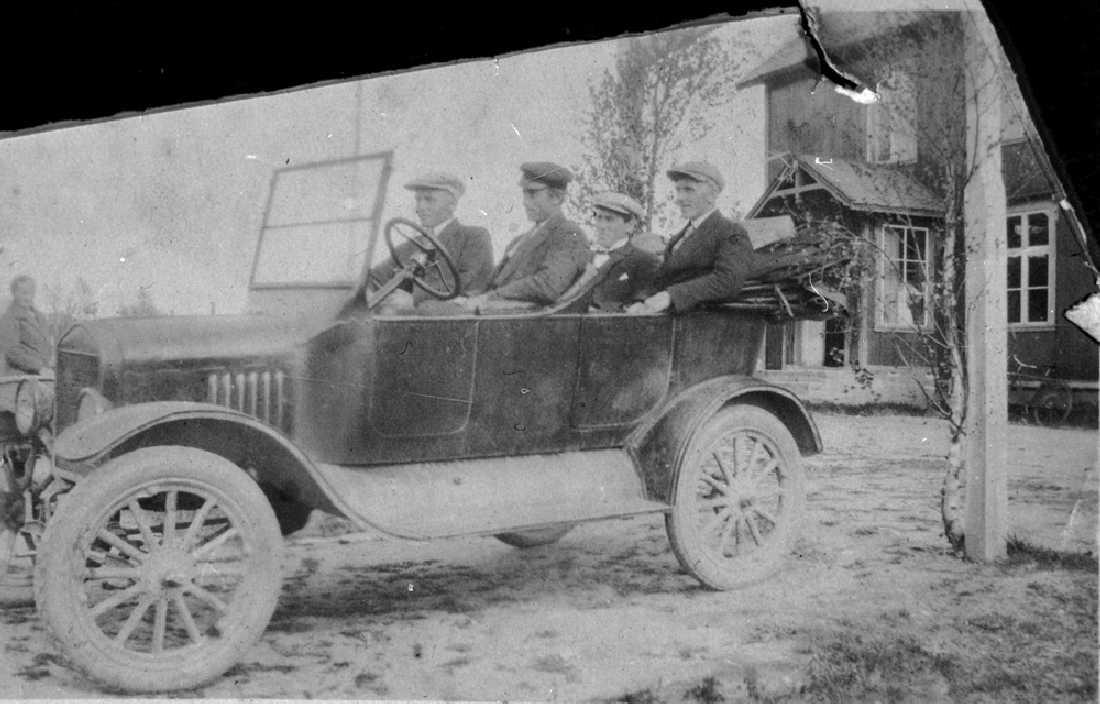 Leirfjord, Ulvangen. Leirfjords første bil, den tilhørte Mathis Simsø. Ved rattet: Mathis Simsø, til h. for han Karl Seime. De to personene bak er ukjente. Bildet er brukt i Leirfjordkalenderen - juni 1986