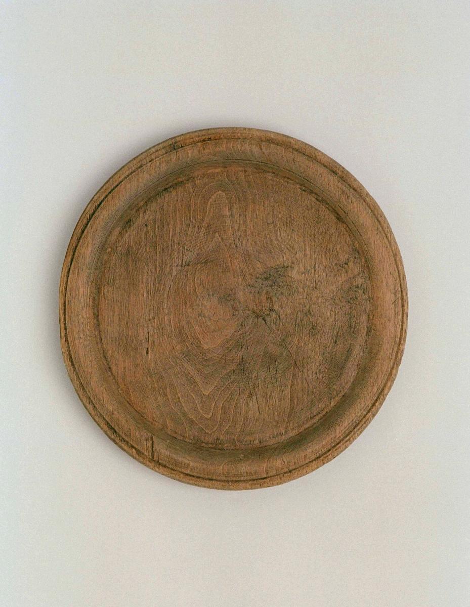 Tallrik av trä, svarvad, flat. Brätte med insvarvad fåra på kanten. På undersidan 1 inristat bomärke. Tillstånd: urflisad på mitten samt på brättet.