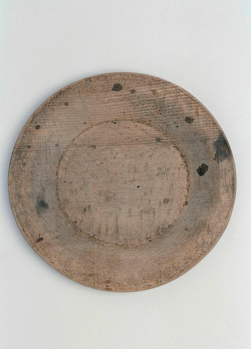"""Tallrik av trä, svarvad. Flat, brätte med insvarvad fåra i kanten som delvis är utnött. På baksidan inbränt """" LOS """"."""