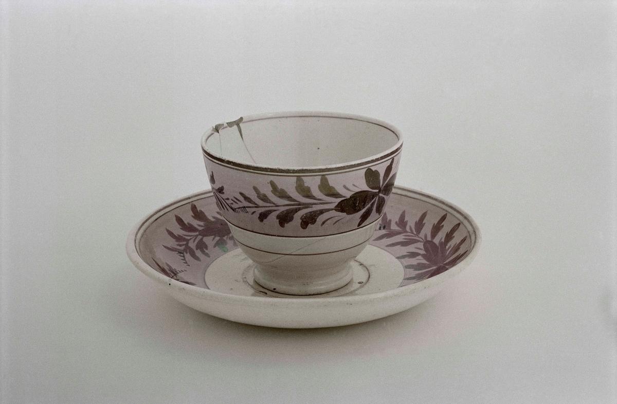 """Kaffekopp med fat. A) Kopp av keramik utan hänkel. Rosa fält mot vit botten med blomdekor i rosa, lysterglasyr. Många lagningar. B) Fat som ovan. Stämplad """" G / Rörstrand """"."""
