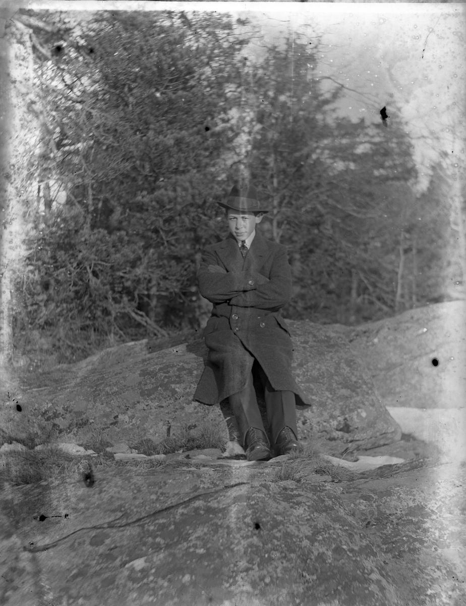 Hugo Larsson i hatt och rock sitter på en sten och tittar in i kameran.