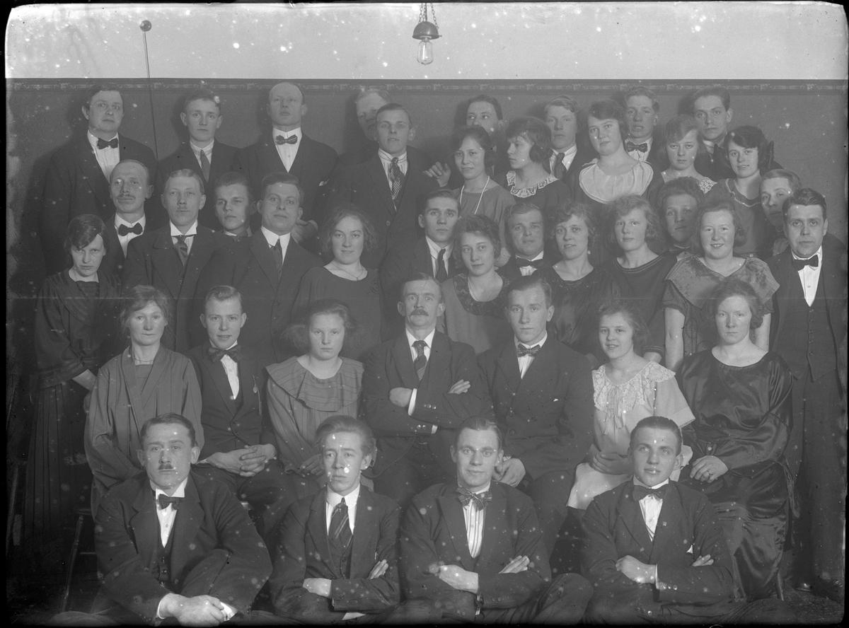 """Gruppbild på kvinnor och män uppställda i fem rader. I fotografens egna anteckningar står det: """"Grupp på 1/10 person. slaktare & bagare""""."""