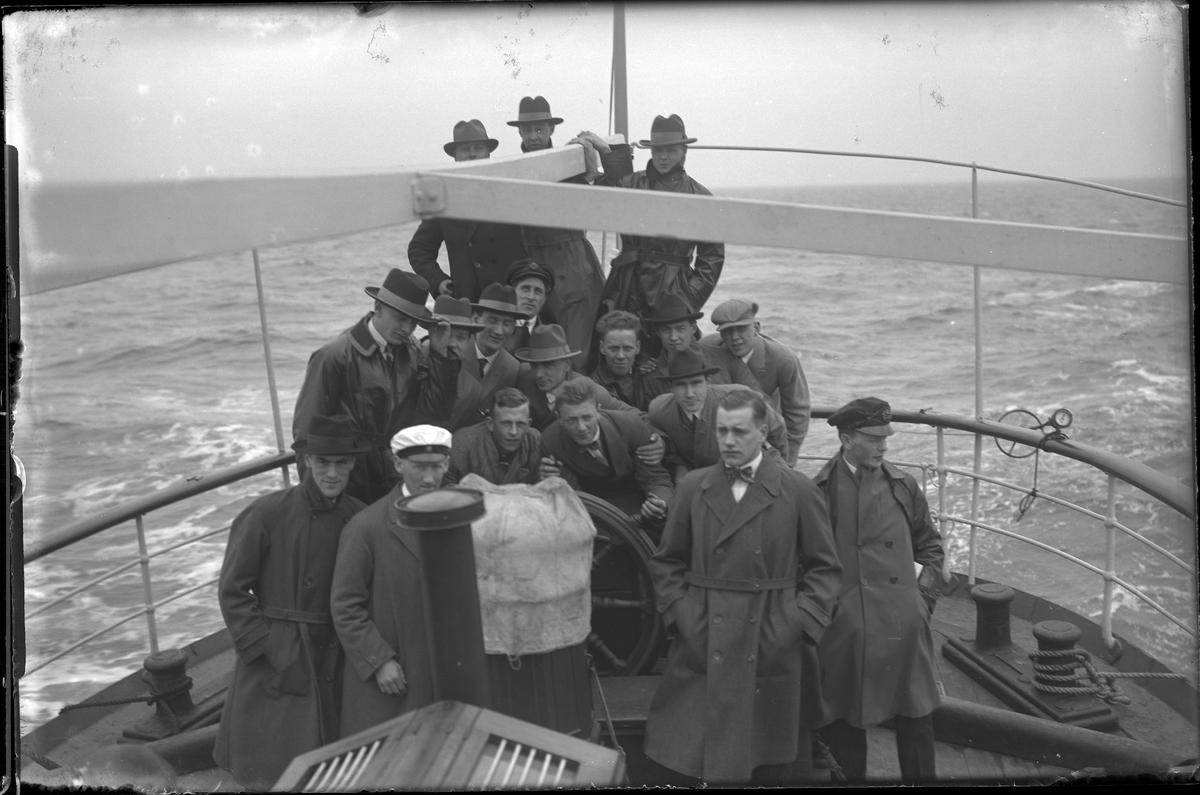 Ett antal män, de flesta i rock och hatt, fotograferade på båtresa. Troligen tillhör de Alingsås Idrottsförening. I fotografens egna anteckningar står: Danmarksresan, På akterdäck.