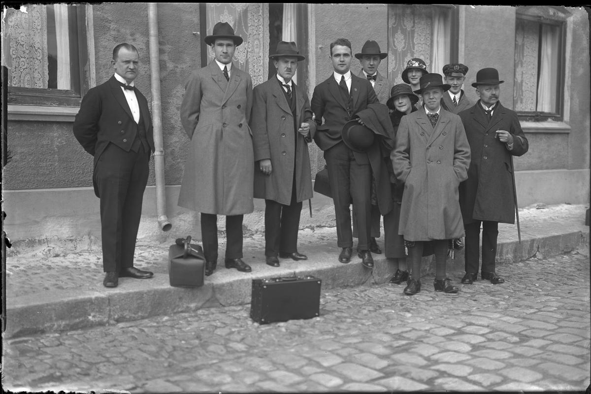 """Tio personer står på en kullerstensklädd gata med trottoar. I fotografens egna anteckningar står: Danmarksresan, """"Harmonien"""""""