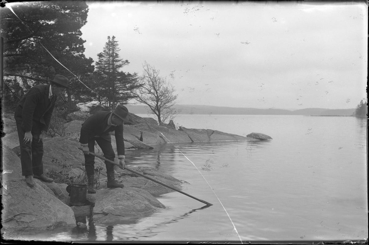 Harald Olsson fångar äling (äldre namn på fisken elritsa) medan Hugo Larsson står bakom och tittar på medan han röker pipa.