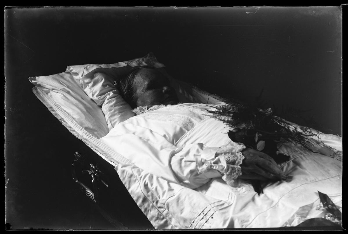 Tilda Pettersson fotograferad avliden med en blombukett i handen liggande i sin kista. Kistan har dekorerats med liljekonvalj.