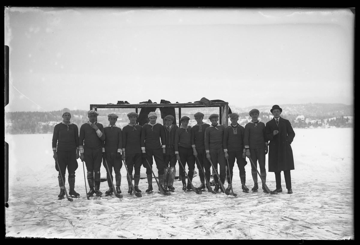 Ett bandylag står uppställda på isen framför ett bandymål. Bredvid står en man i ytterrock och plommonstop och röker.