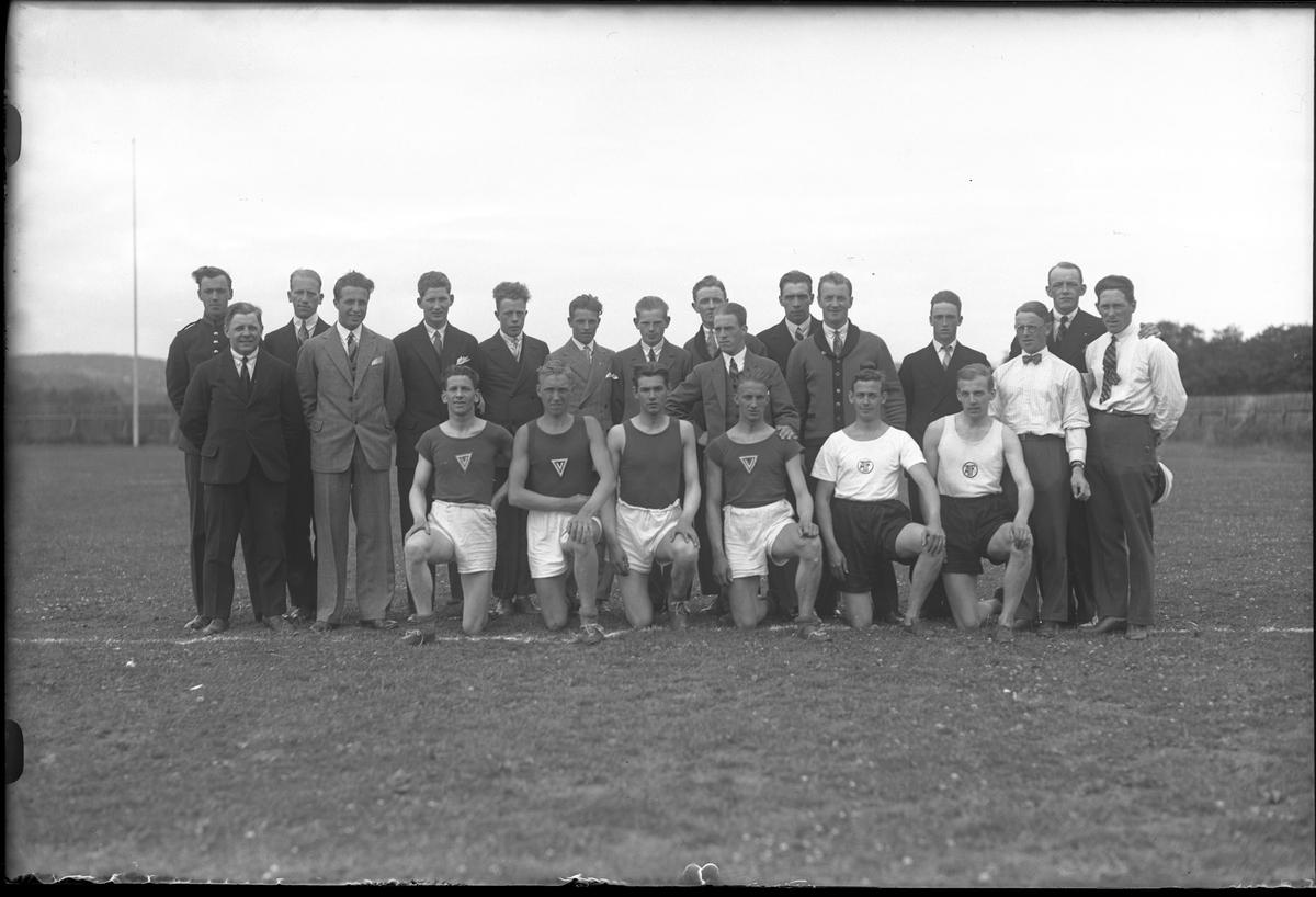 """En grupp män står samlande på en idrottsplats. De i främreraden har idrottskläder medan de bakre bär kostym. I fotografens egna anteckningar står det """"Deltagare i tävl. Viking, Gbg - A.I.F"""""""