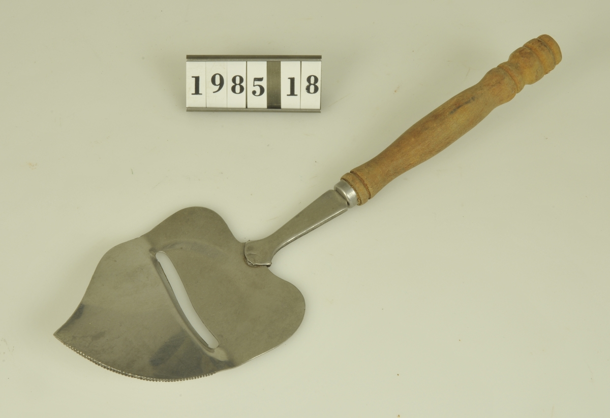 Osthyvel av rostfritt stål med svarvat träskaft.  Kommer från Kv. Friden.