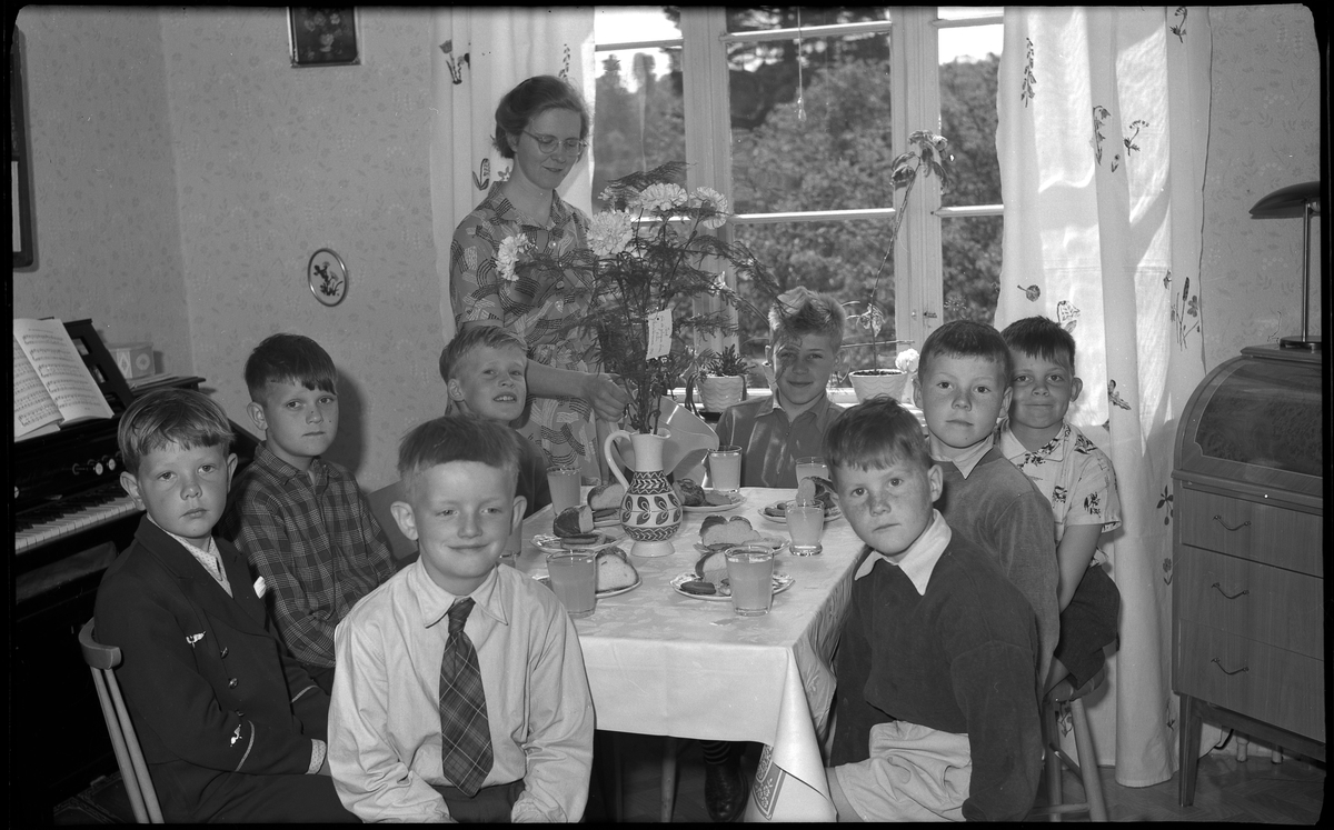 En interiör från ett rum i ett äldre trähus, ett dukat bord står vid fönstret, rakt ut från väggen.   Runt bordet sitter åtta pojkar, sju-tio år. De går i klass 1, 2 och 3. Framför varje pojke står ett glas saft och en assiett med en slät bit bulle och en småkaka. Nyberg häller precis upp ett glas saft åt en av pojkarna.  Nära fönstret, till vänster om bordet, står lärarinnan Signhild Nyberg. Framför henne står en bukett nejlikor i en keramikvas. I buketten sitter ett tack-kort.   Till vänster i bild syns ett piano och till höger syns en sekretär. Gardinerna består av två raka längder, ljusa med nåt mönster, duken är enfärgat ljus  Någon form av avslutningsfest,  Foto 12 juni 1956.