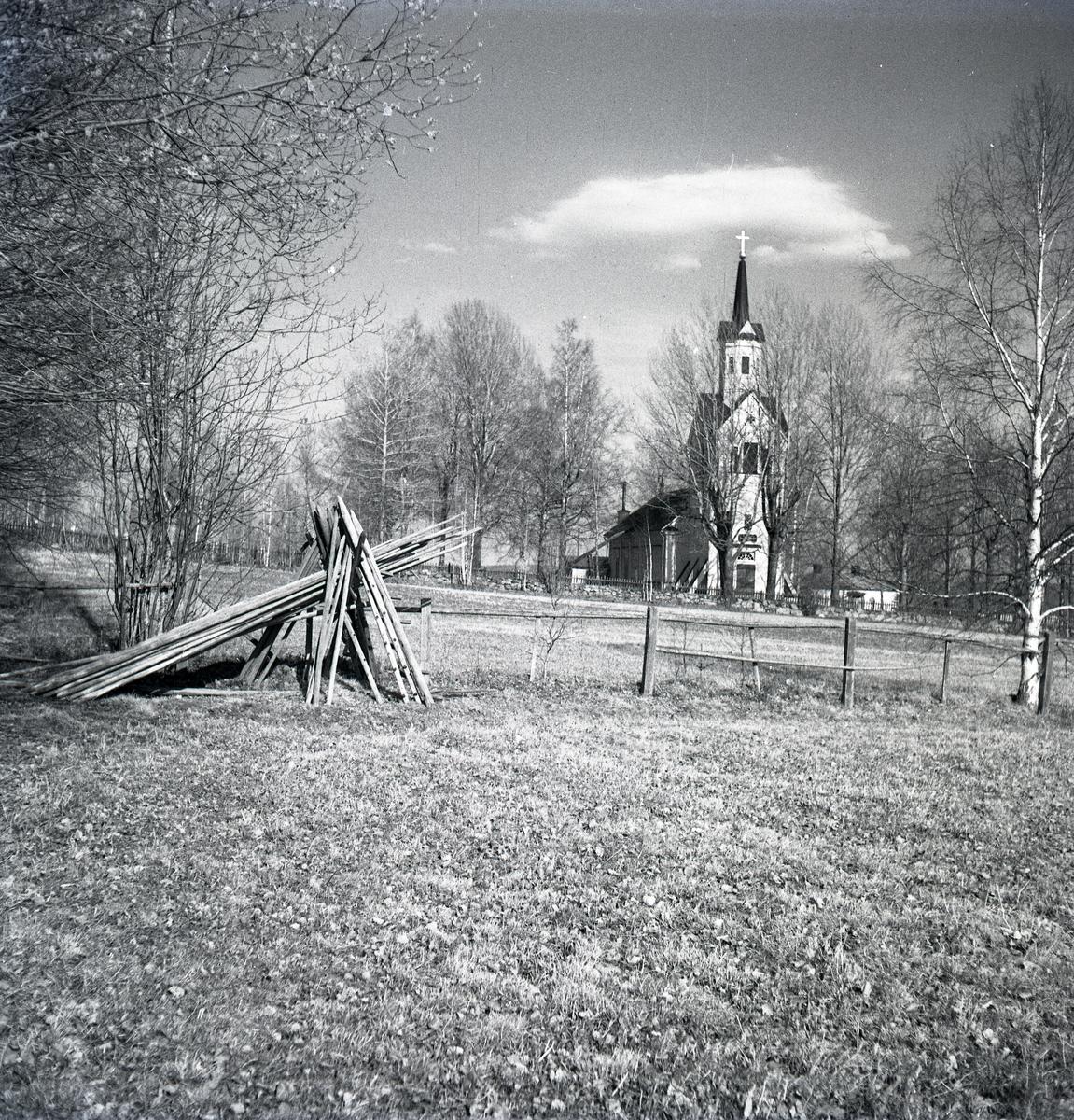 Los kyrka bakom en ställning hässjevirke på ett fält.
