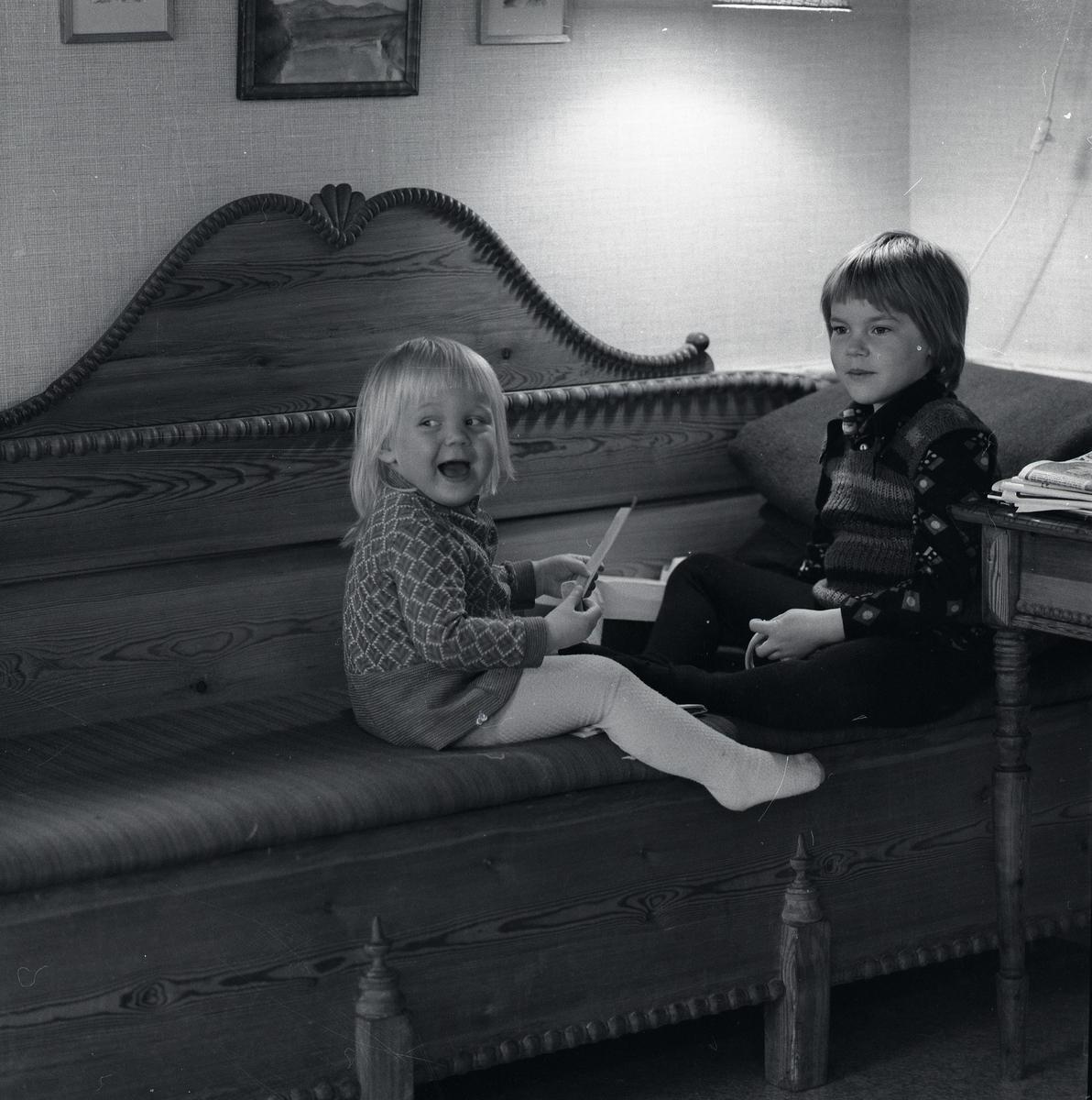 Två barn sitter på en soffa och leker.