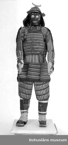 """Ur gåvobok från 1901: """"Den 30 februari 1901 inköptes en japansk krigarutrustning bestående av hjälm, pansarklädnad för hela kroppen och ... samt båge med pilar. Den har tillhört en japansk riddare (s.k. Daimyo) under förra hälften av 1800-talet. Den kostade vid inköp från herr Ryberg i Göteborg 100 kronor. Konstnären Arthur Brattberg i Uddevalla erhöll 25 kronor för en av honom förfärdigad stomme till nämnda krigarutrustning 21/1 1902.   Ur handskrivna katalogen 1957-1958: Jap. riddarrustning a) H c:a: 170 cm; monterad på en tygklädd fotplatta. (Vid inv. juli-58 ej uppackad, varför noggrannare uppg. sakn. b) Hjälmen .I. L. c:a (utom nackskydden) c:a 17,5 cm; på hjässan ett hål m. mäss.beslag;; 4 rörliga markplåtar av bakelitlikn. material; b:II hjälmprydnad, form av månskära; 14 x 10 cm. c) Spjutet; total L. 218 cm; I= skaftet, m. en tvärgående vinkelböjd järnstång; upptill svart och rött.c) II=spjutspetsen, L. 29,5 cm; järn. III= skydd f. spetsen; av trä; L.26 cm; svartlackerat m. skrovl. yta. d) Båge; L.215 cm; mörkbrun blank yta, virad m. ljusare bruna trådar.  e) 10 st fjädrade pilar, m. korta spetsar av järn; L c:a 90 cm; i en ställning av trä.  Pilarna = e: 1-10. Föremålen hela."""