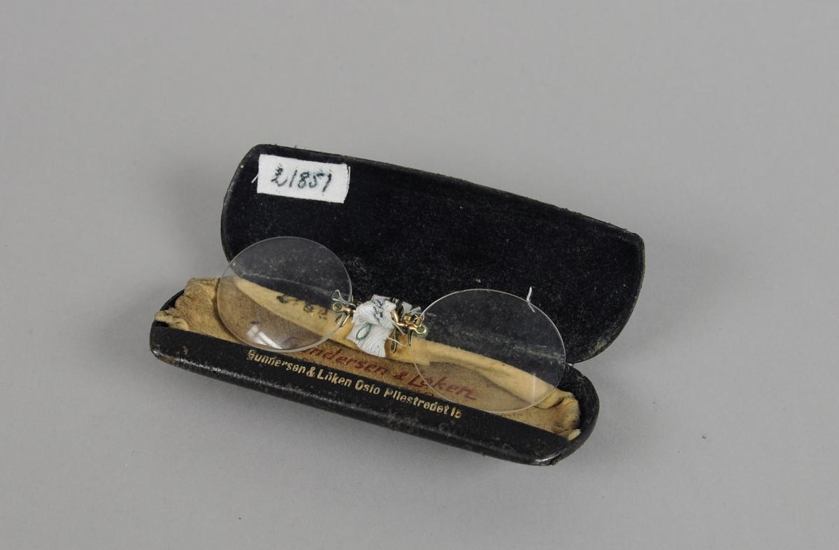 Brilleetui av metall med svart trekk, som åpnes på langsiden. Svart fór. I etuiet er det en lorgnett og en pusseduk.