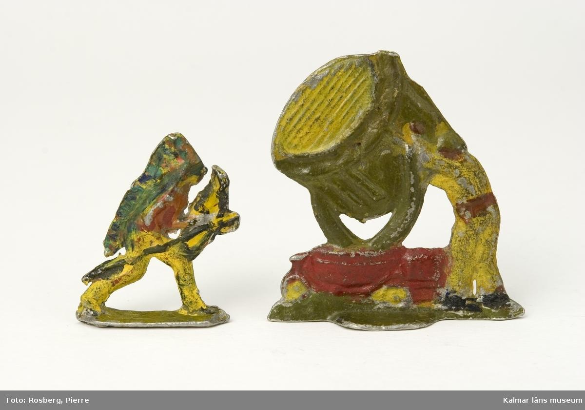 KLM 43767:5:1-2. Tennfigur. Tennsoldat. 2 stycken udda, platta figurer. :1 en soldat som riktar en stor strålkastare som är monterad på en hjulburen vagn, 1930-40-tal, andra världskrigets luftvärn, målad i rött, gult, grönt och svart. :2 en indian med pilbåge, kladdigt målad i rött, gult, grönt och svart.