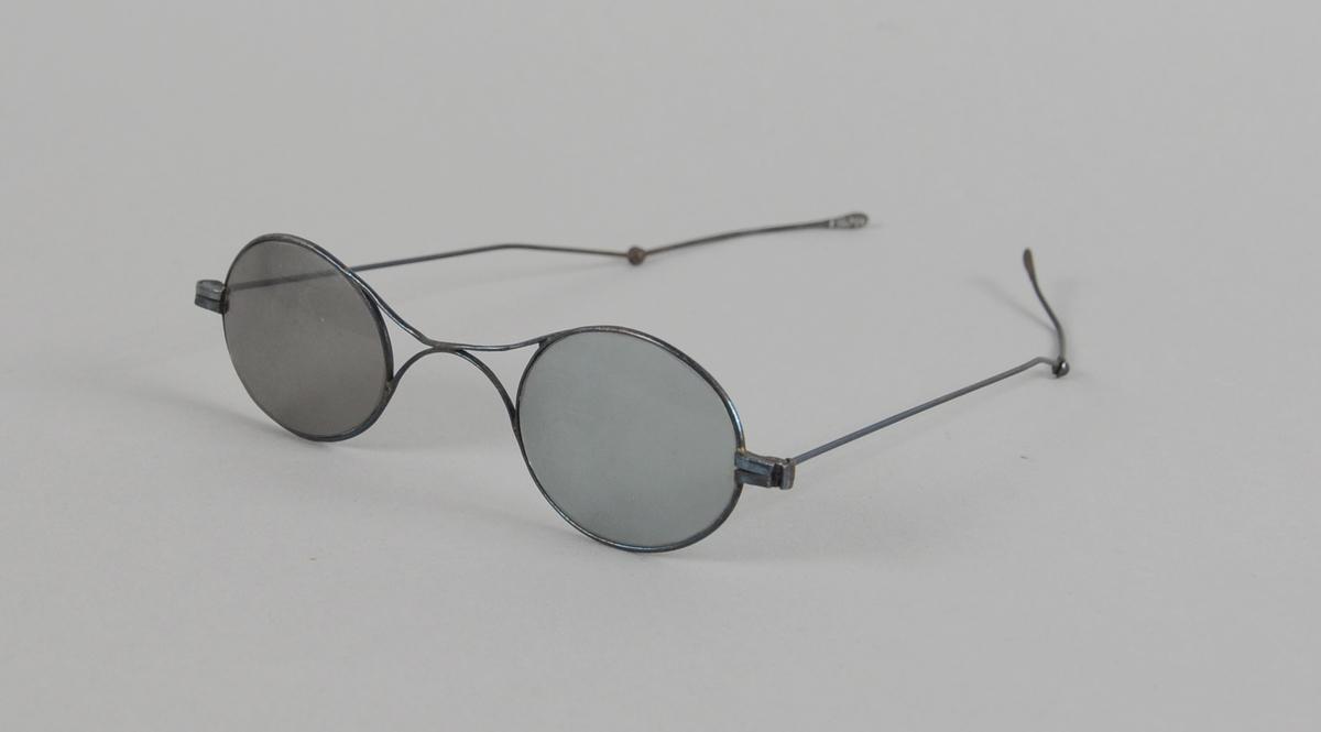 Ovale briller med mørkt glass og metallinnfatning. Stengerne kan brettes ut.