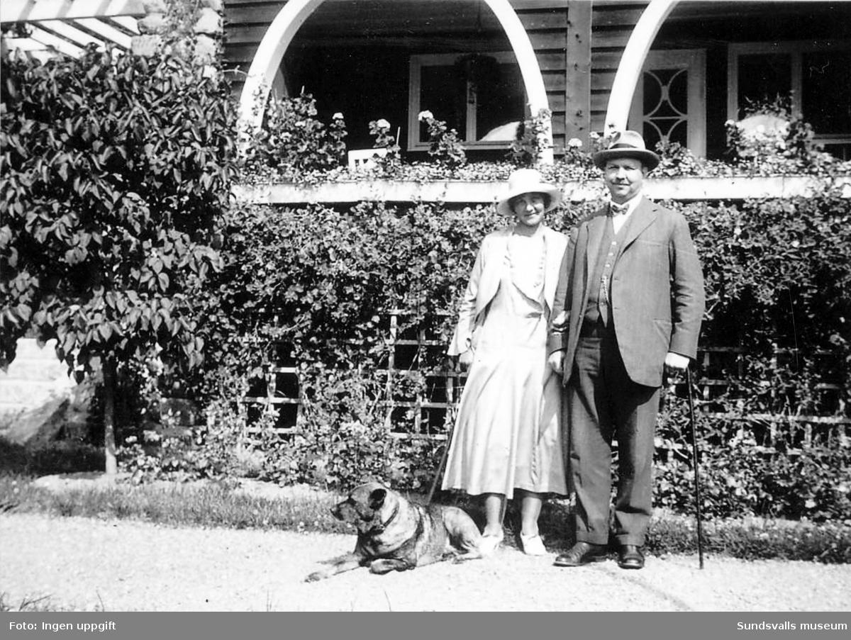 """Grosshandlare (järnhandlare) Wilhelm Österberg (f. 1882 d. 1941) med fru Ella (f. 1884 d. 1975) vid sommarbostaden """"Villa Granliden"""" i Stenvik, Alnö. Huset uppfördes 1917."""